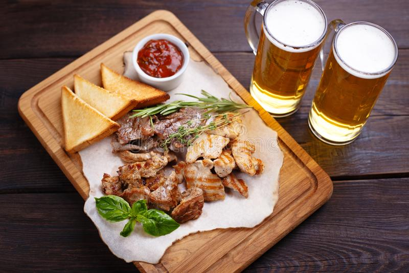 Beer snacks. Grilled pork, chicken, beef on plate royalty free stock photo