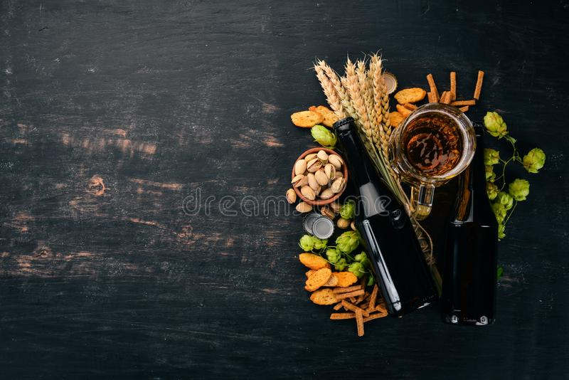 Beer and snacks. Salted crackers, Dried Fish, Chips, Nuts, Peanuts, Pistachios. On a black wooden background. Free space for text. Top view royalty free stock images
