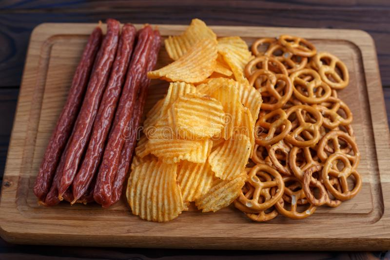 Beer snacks set close up. Pretzel crackers, chips and sausages o. N the board. Oktoberfest food, pub concept royalty free stock image