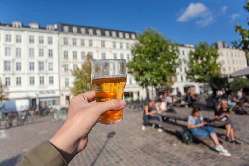 Beer of street drinker in park with relaxing people of Copenhagen, Denmark. Leisure in Scandinavia with drinks and food.  stock photos