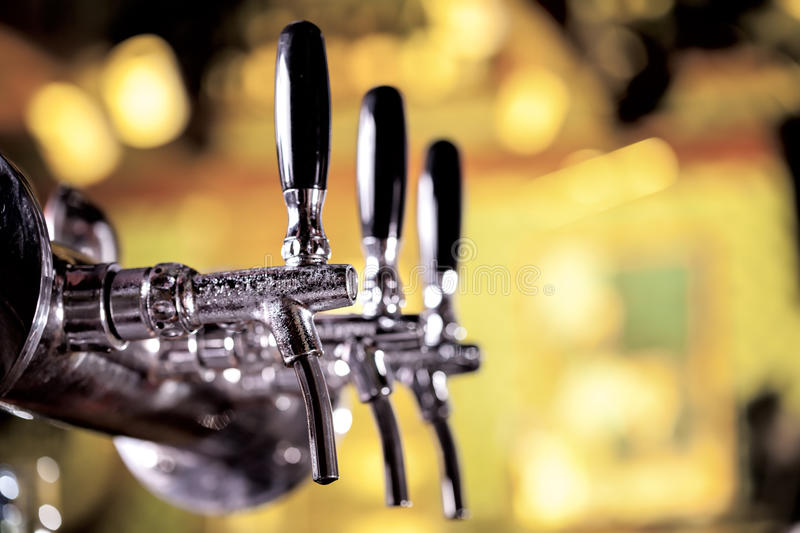 Beer tap. With golden beer-toned background stock images