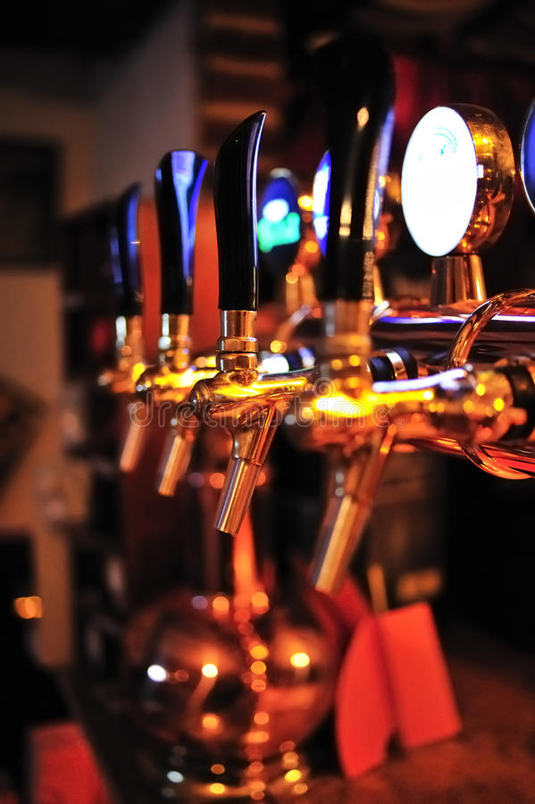 Beer tap in the pub. Golden beer tap with black handles in the pub royalty free stock photo