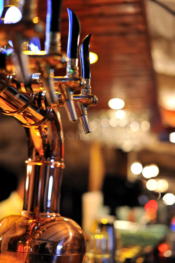 Beer taps in the pub. Golden stainless beer taps system at the pub bar stock photos