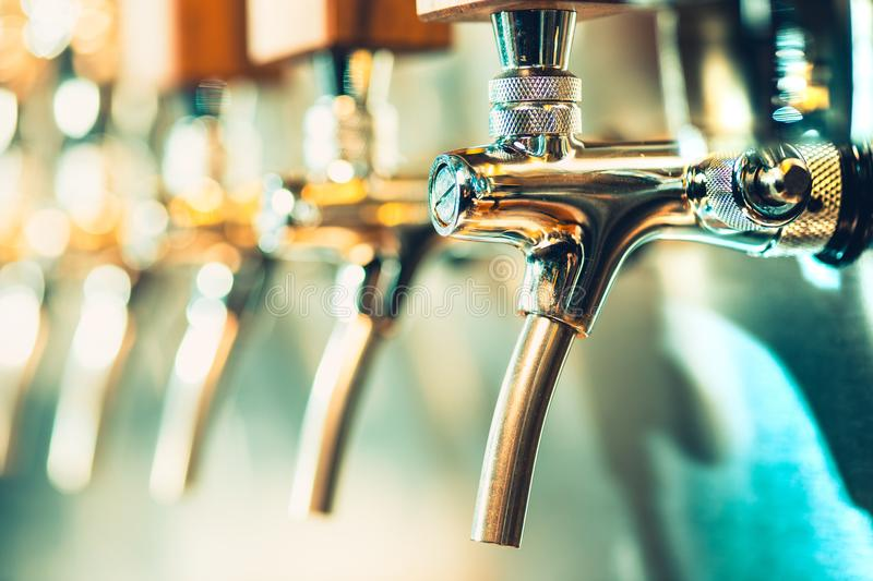 Beer taps in a pub. The beer taps in a pub. nobody. Selective focus. Alcohol concept. Vintage style. Beer craft. Bar table. Steel taps. Shiny taps