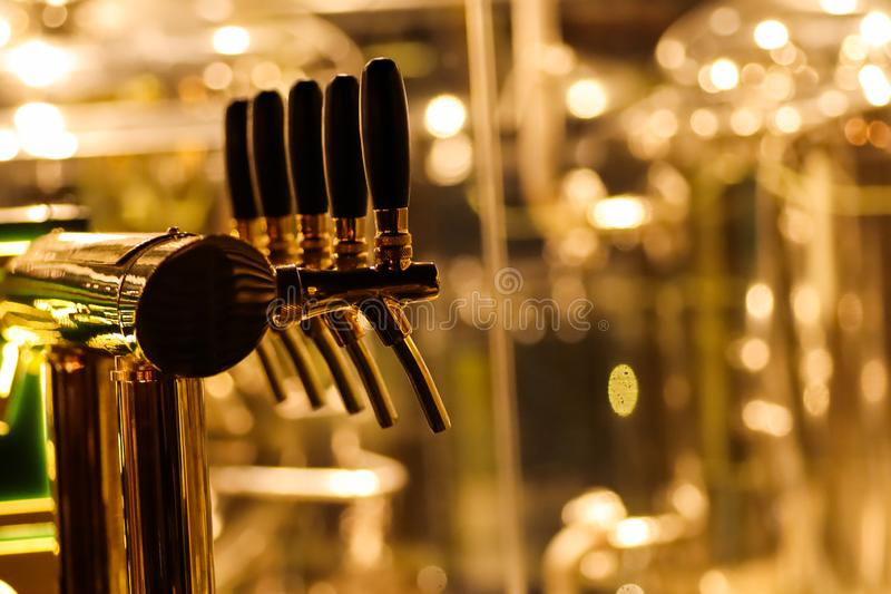 Beer taps to dispense beer in mug with selective focus and distillery in background of a brewery.  stock photography