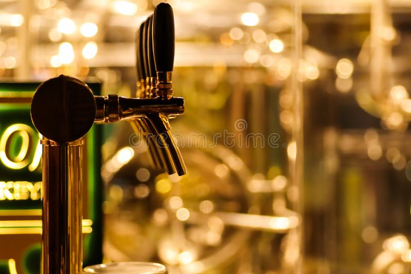 Beer taps to dispense beer in mug with selective focus and distillery in background of a brewery.  stock image