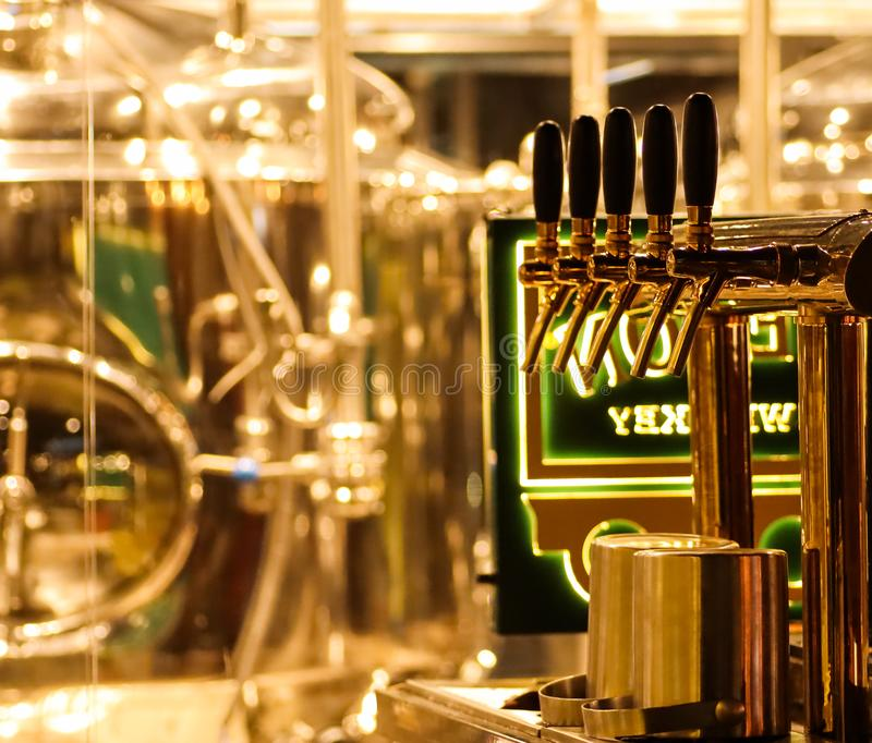 Beer taps to dispense beer in mug with selective focus and distillery in background of a brewery.  royalty free stock image
