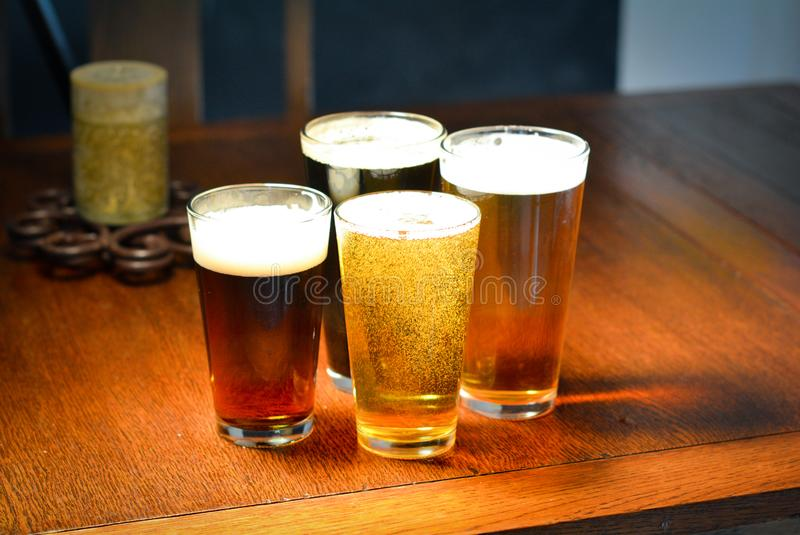 Beer Tasting with Four Beers on a Wooden Table. Four pints: a lager, stout, ale and a smooth bitter on a wooden table or bar ready for beer tasting stock image