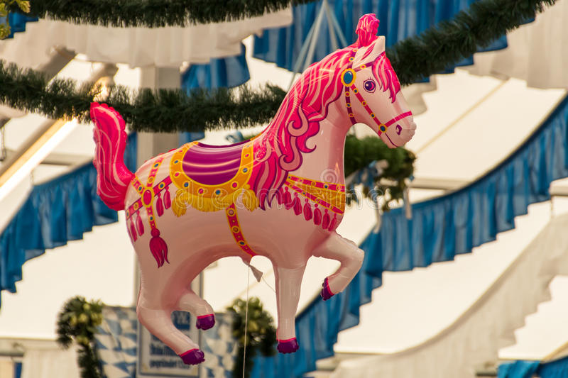 Beer tent at Spring Festival on Theresienwiese in Munich, German. Pink horse balloon in a beer tent with the decorated roof of the beer tent in the background stock photo