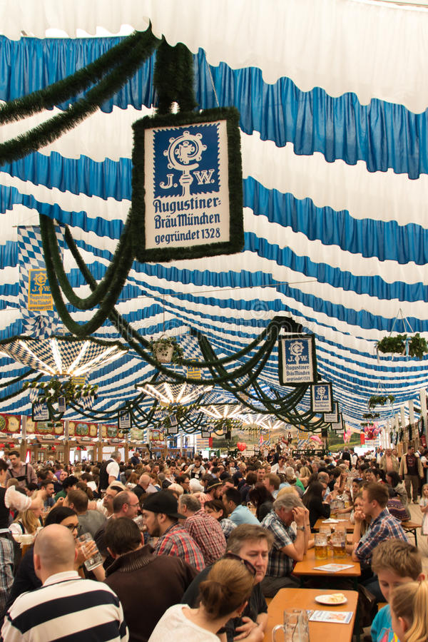 Beer tent at Spring Festival on Theresienwiese in Munich, German. Traditional dressed people with dirndls and leather trousers in a beer tent on Theresienwiese stock photo