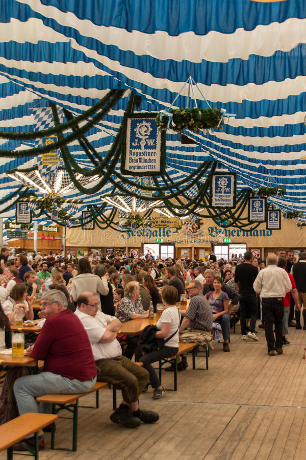 Beer tent at Spring Festival on Theresienwiese in Munich, German. Traditional dressed people with dirndls and leather trousers in a beer tent on Theresienwiese royalty free stock images