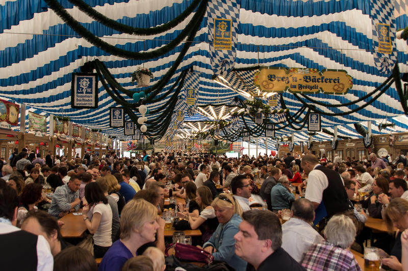 Beer tent at Spring Festival on Theresienwiese in Munich, German. Traditional dressed people with dirndls and leather trousers in a beer tent on Theresienwiese royalty free stock photography