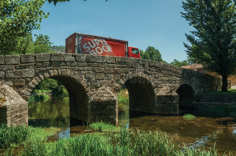 Beer truck passing over old bridge on the Sever River in Portagem. Marvao, Portugal - July 09, 2018. Beer truck passing over the old Roman stone bridge on the royalty free stock photo