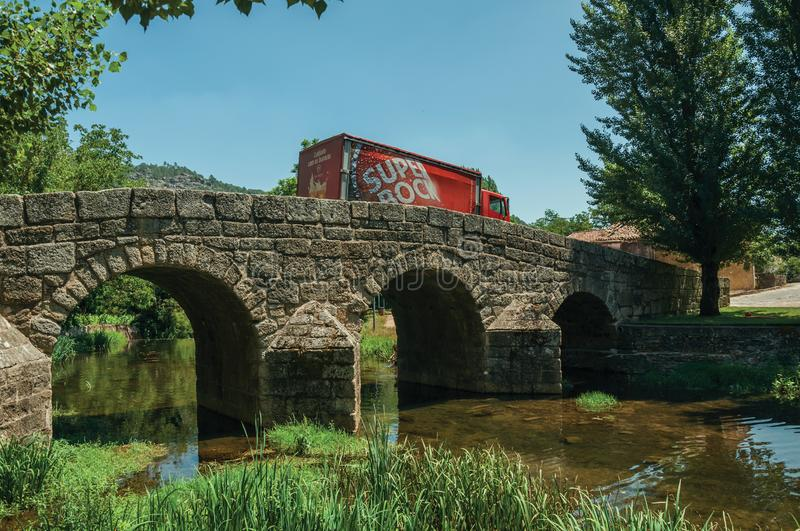 Beer truck passing over old bridge on the Sever River in Portagem. Marvao, Portugal - July 09, 2018. Beer truck passing over the old Roman stone bridge on the royalty free stock photos