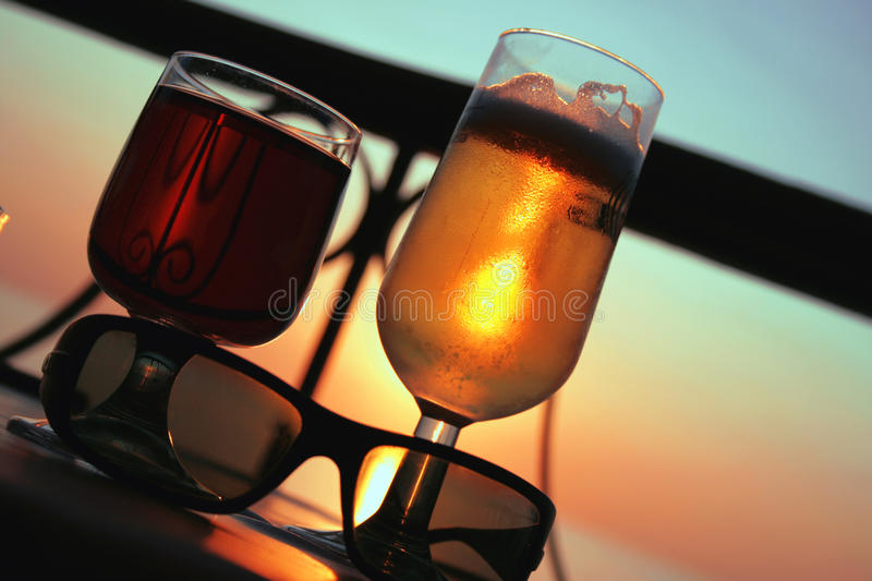 Beer and wine. A shot of two glasses of beer and wine at sunset