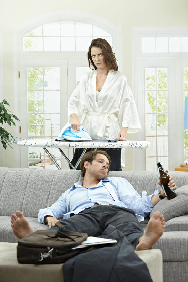 Beer after work. Tired businessman resting on couch with beer in hand. Angry wife ironing in the background royalty free stock photo
