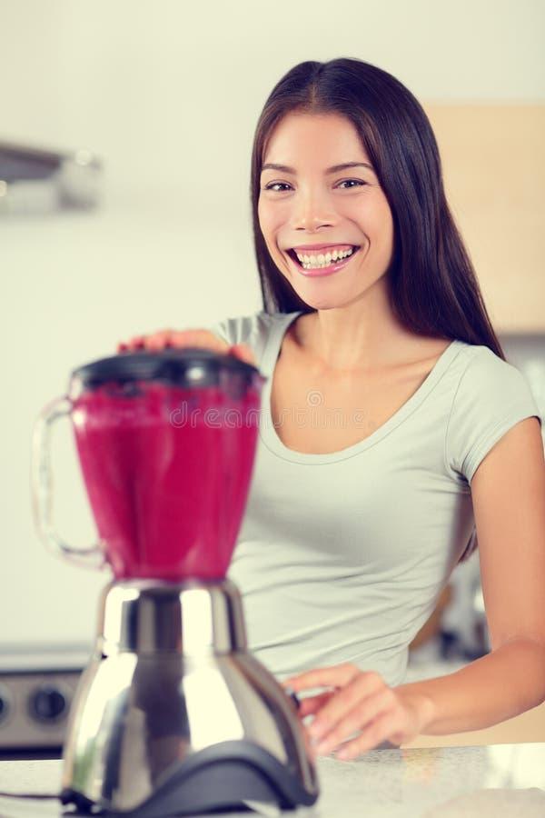 Beere Smoothiefrau, die Frucht Smoothies macht lizenzfreies stockfoto