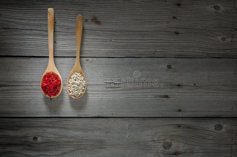 Beeren des weißen Pfeffers und des goji auf hölzernen Löffeln und hölzernem Hintergrund stockfotos