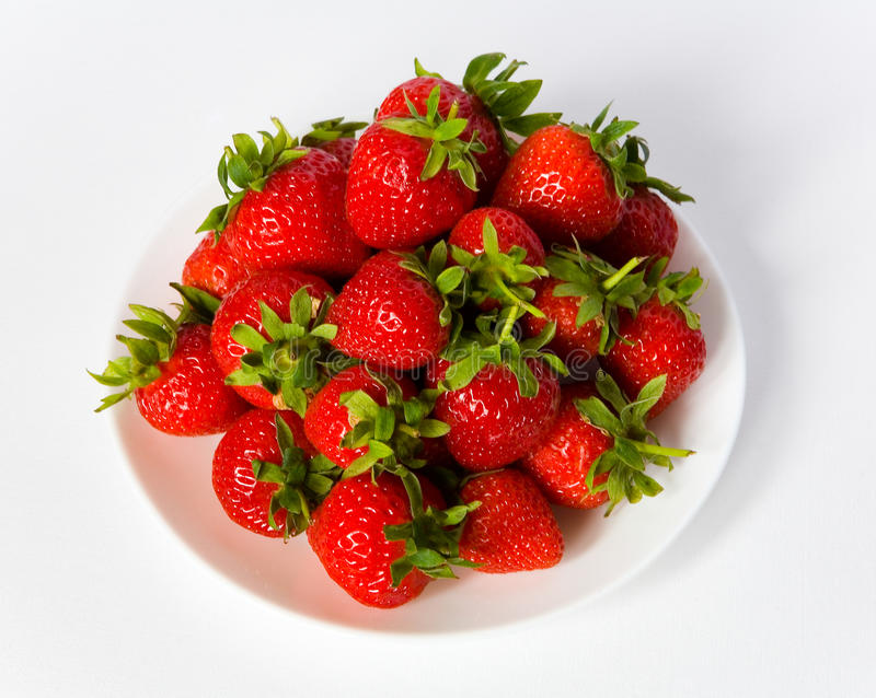 Beeren einer Erdbeere auf einer weißen Platte lizenzfreies stockbild