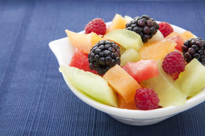 Beeren und gewürfelte Melone in einer Schüssel auf der Tabelle lizenzfreie stockbilder