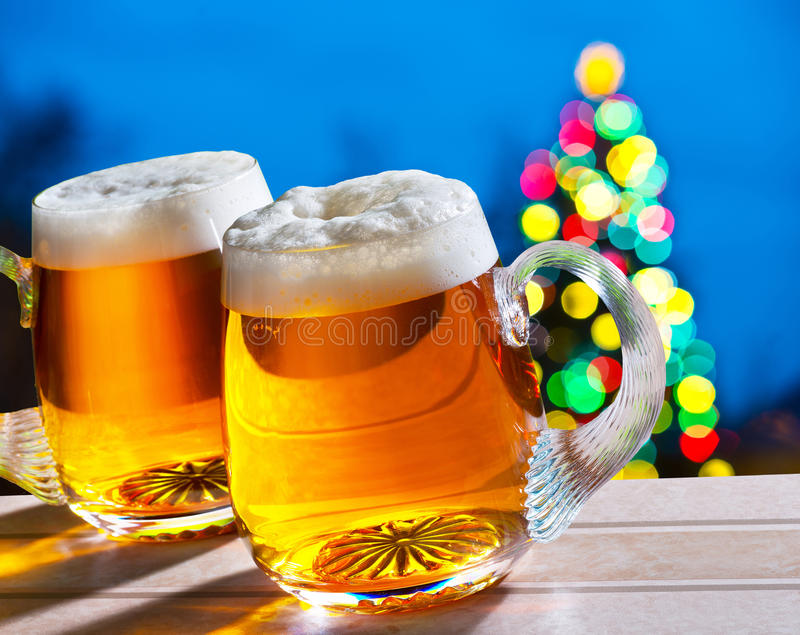 Beers and Christmas tree. Two beer glasses with colored Christmas tree stock photography