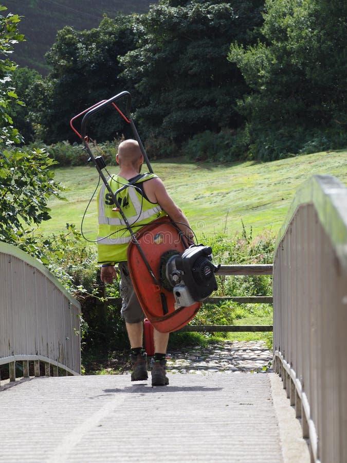 BEESTON, CHESHIRE/UK - 16. SEPTEMBER: Mann, der einen Rasenmäher a trägt stockbilder