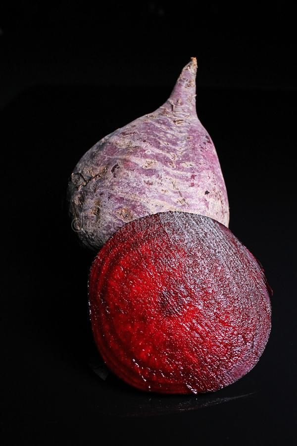 Beet beetroot. Whole and half cutted beet beetroot on black reflective studio background. Isolated black shiny mirror mirrored bac. Kground for every concept stock image