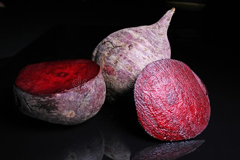 Beet beetroot. Whole and half cutted beet beetroot on black reflective studio background. Isolated black shiny mirror mirrored bac. Kground for every concept royalty free stock photos