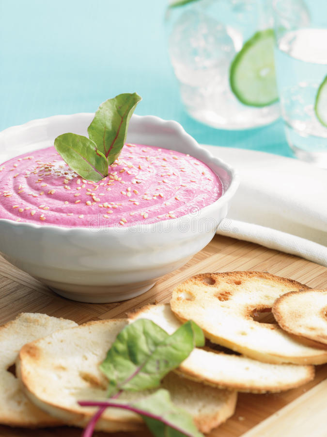 Beet garlic dip. With sesame seeds garnished with beet leaves. Serve on wood board with grilled bagel. Two glasses of lime water in the background stock images