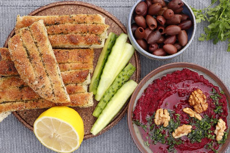 Beet hummus with olives and bread stock photo