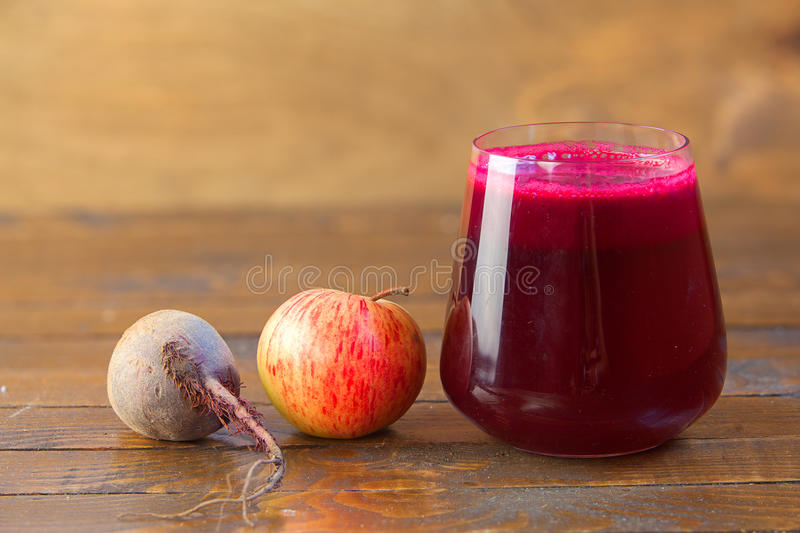 Beet juice in glass on table. Beet juice in glass on wooden table royalty free stock photo