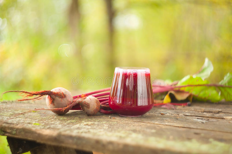 Beet juice in glass on table. Beet juice in glass on wooden table royalty free stock photos
