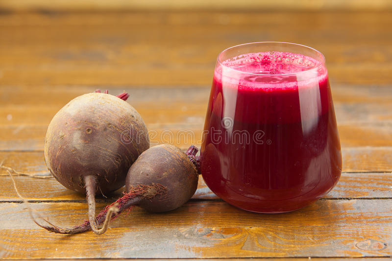 Beet juice in glass on table. Beet juice in glass on wooden table stock photos