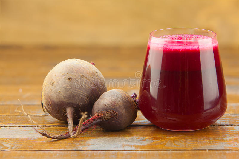 Beet juice in glass on table. Beet juice in glass on wooden table royalty free stock images