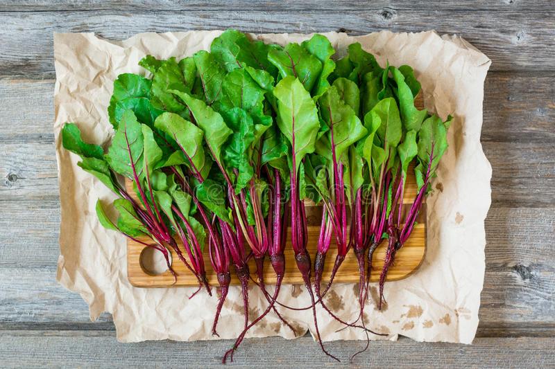 Beet roots on craft paper. Young fresh beet roots on crumpled craft paper and rustic wooden background royalty free stock photos