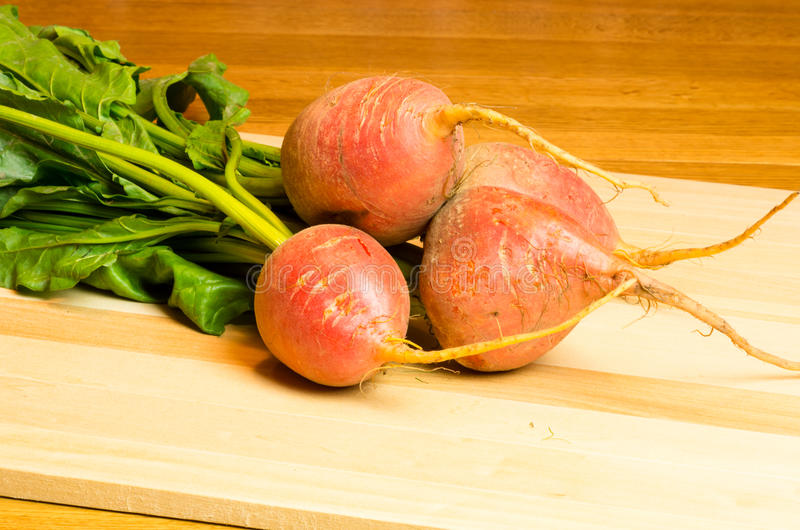 Beet roots on wooden cutting board. Fresh beets on wooden cutting board ready to slice stock photos