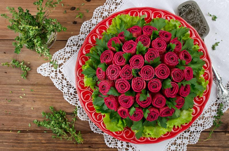 Beet salad with pancakes in the shape of a bouquet of roses. Decoration is made of pancakes royalty free stock photo
