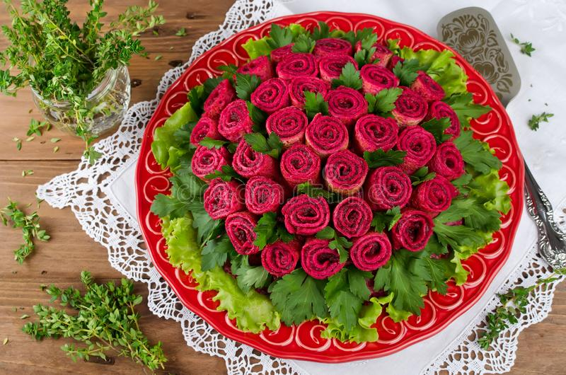 Beet salad with pancakes in the shape of a bouquet of roses. Decoration is made of pancakes royalty free stock image