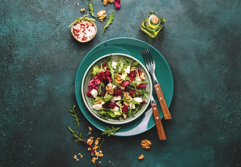 Beet summer salad with arugula, radicchio, soft cheese and walnuts on plate with fork, dressing and spices on blue kitchen table, stock photography