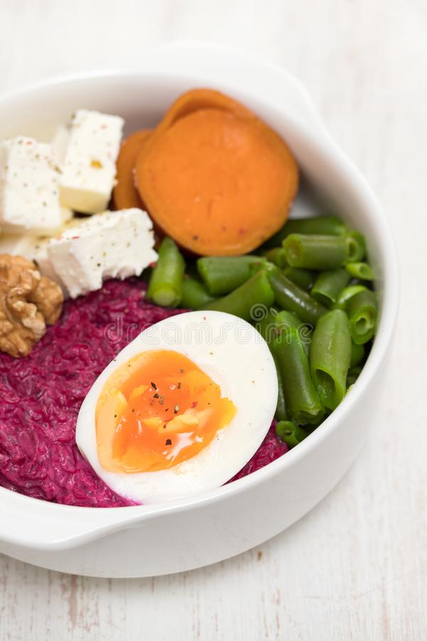 Beet, sweet potato, nuts, green beans and boiled egg in white bowl royalty free stock photo