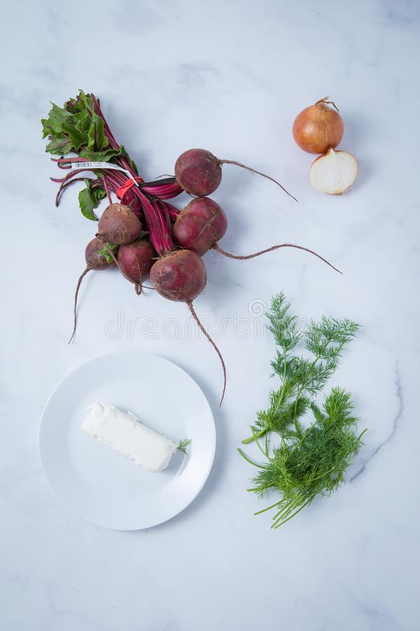 Beetroot Goat Cheese Dill Onion. Top view of raw beetroot, goat cheese on a white plate, onion cut in half and dill. Healthy vegetarian ingredients on a light royalty free stock photo