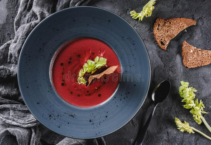 Beetroot kremowa polewka z selerem i croutons w talerzu na zmroku popielatym tle z łyżką i pieluchą Zdrowy weganinu jedzenie obrazy royalty free