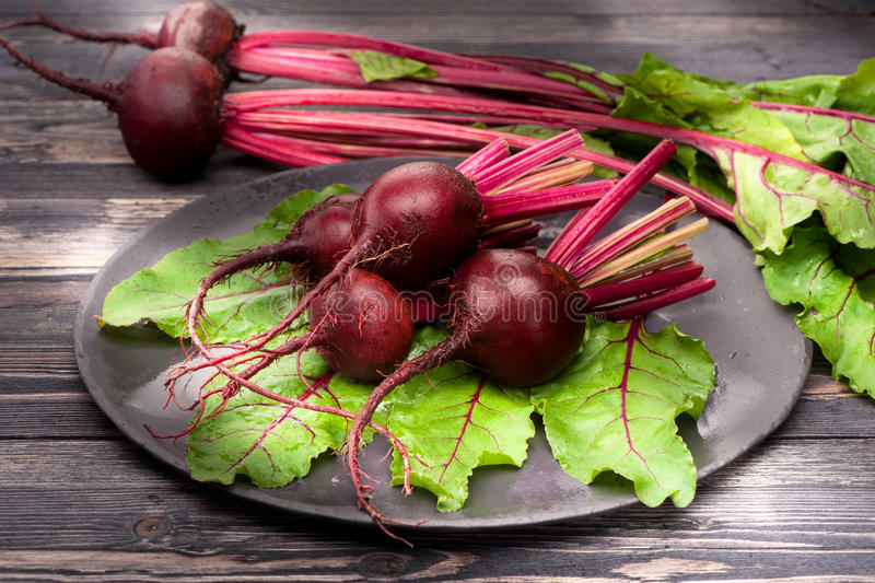 Beetroot with leaves. Fresh beetroot on a plate on a wooden table royalty free stock images