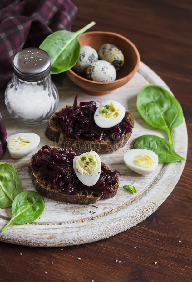 Beetroot relish and a sandwich with beets, quail egg and spinach on rustic light wooden board. Healthy food royalty free stock photography