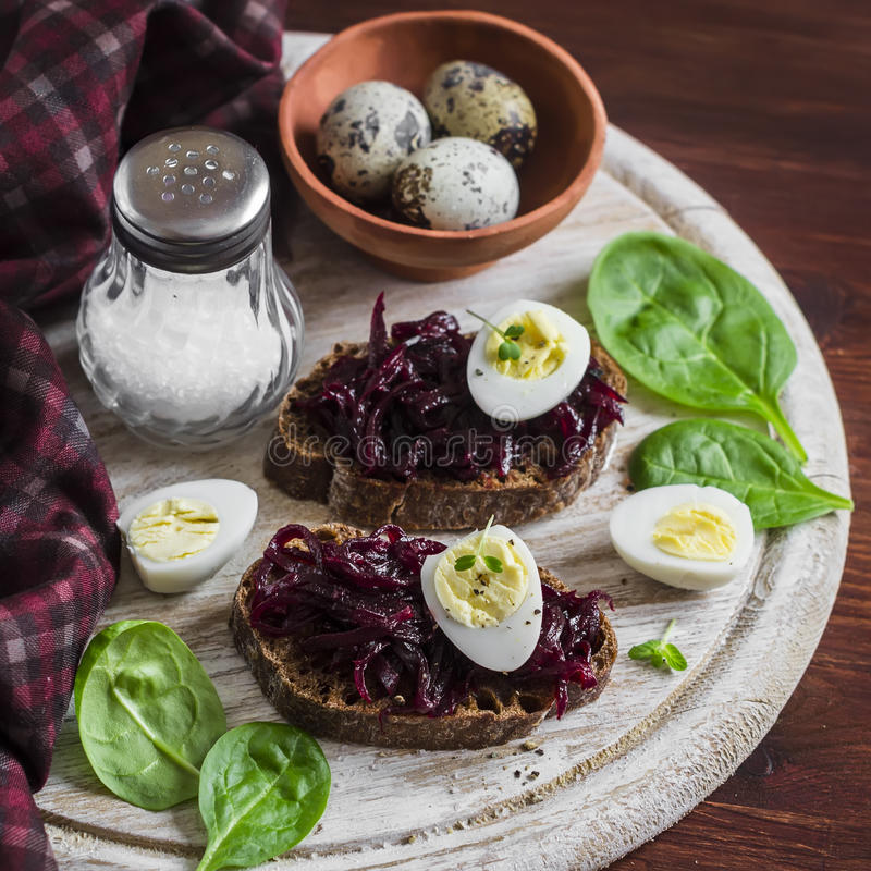 Beetroot relish and a sandwich with beets, quail egg and spinach on rustic light wooden board. Healthy food royalty free stock images