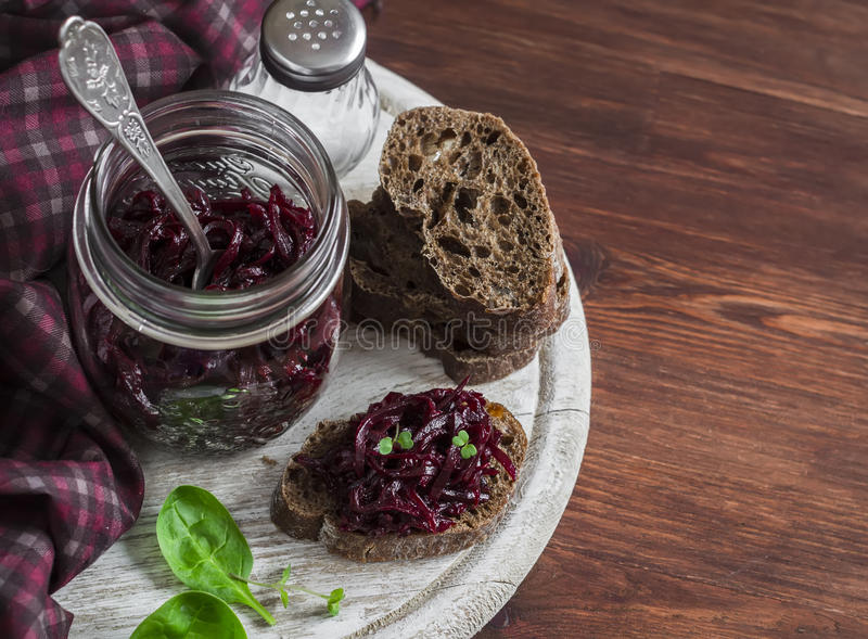 Beetroot relish and slices of rye bread on rustic wooden board. Healthy breakfast or snack. Delicious vegetarian food royalty free stock photos