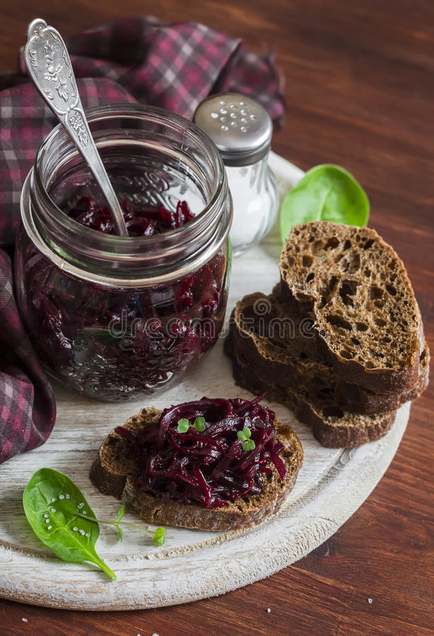 Beetroot relish and slices of rye bread on rustic wooden board. Healthy breakfast or snack. Delicious vegetarian food stock photos