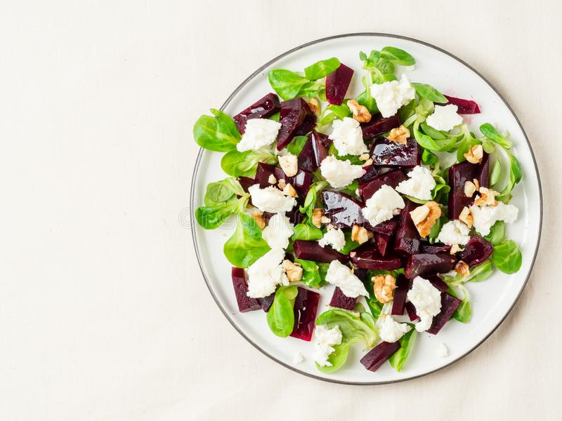 Beetroot salad with feta, cheese, walnuts, corn salad and Brined cheese, pickled on white table, top view, copy space stock images