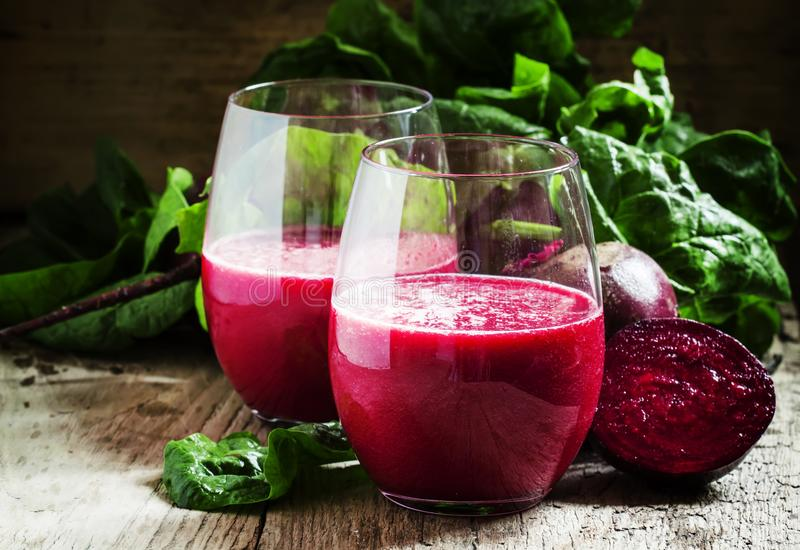 Beetroot smoothie in a large glass, fresh beets with tops, old w stock photography