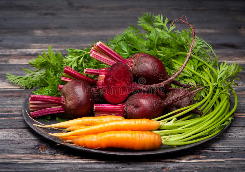 Beets and carrots. On dark wooden background royalty free stock image